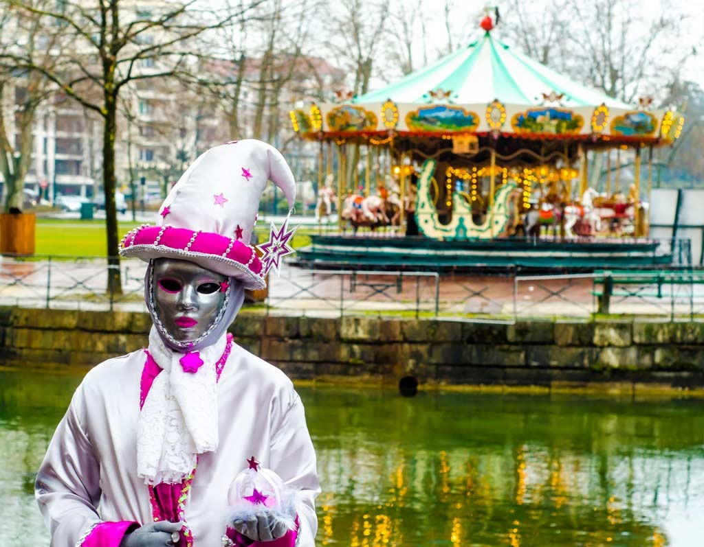 One of the masqueraders across the water from a carousel