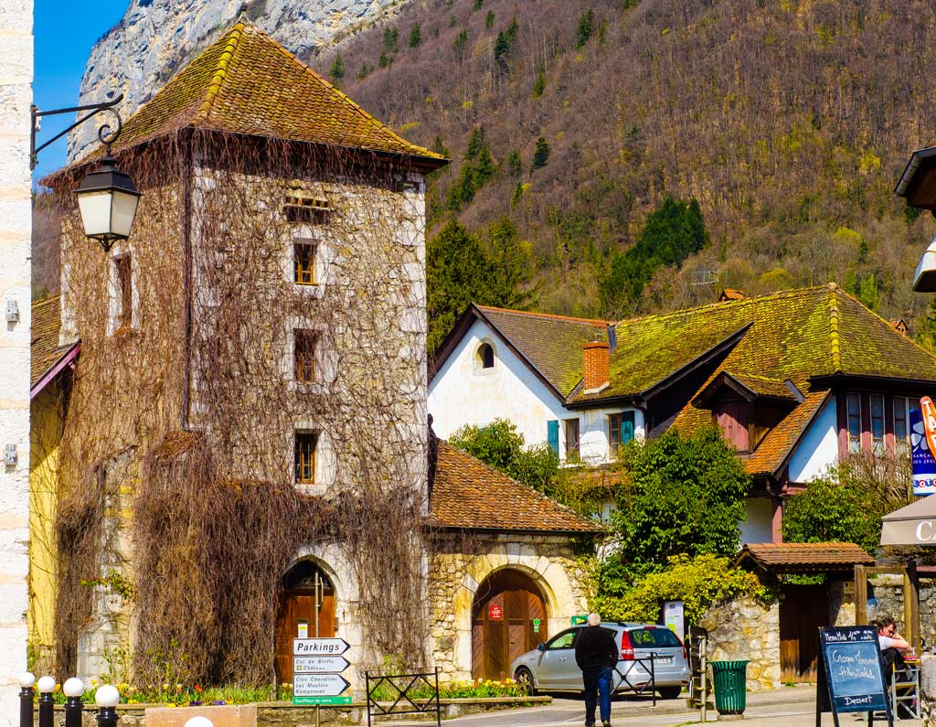 The Centre of Menthon-St-Bernard - in the summer, the tower's vines are covered in thick lush greenery.